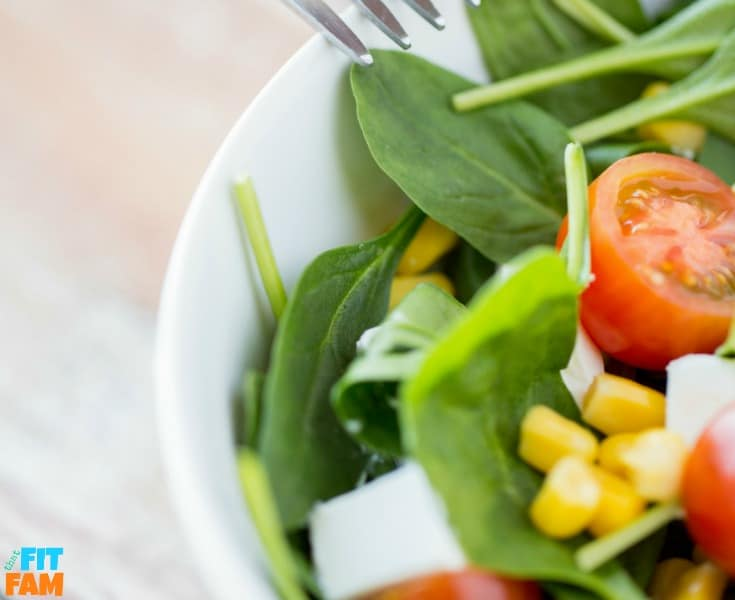 small bowl of salad made with spinach, tomatoes, corn, and other veggies.
