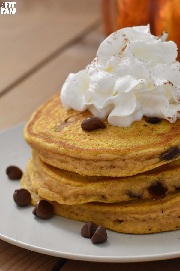 a stack of warm chocolate chip pumpkin pancakes topped with whipped cream & a sprinkle of cinnamon. perfect for Fall.
