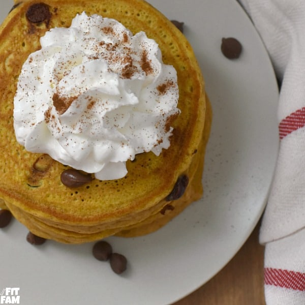 pumpkin chocolate chip pancakes topped with whipped cream & more chocolate chips