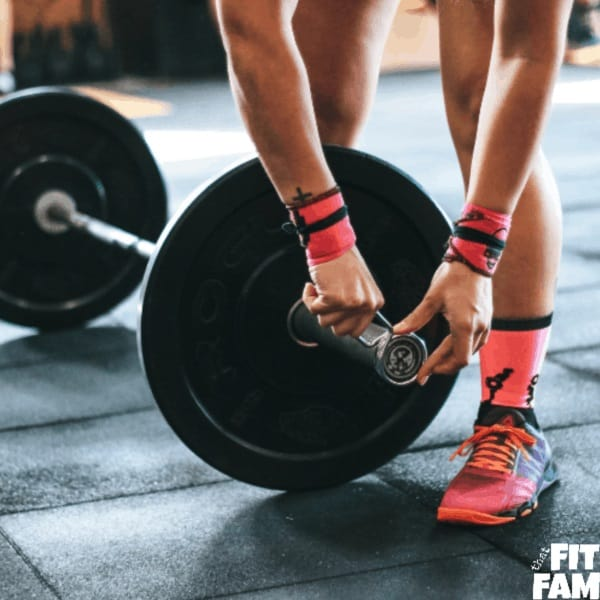 woman loading up barbell for weightlifting routine
