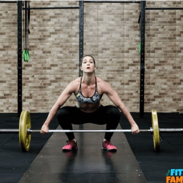girl performing weightlifting using loaded barbell