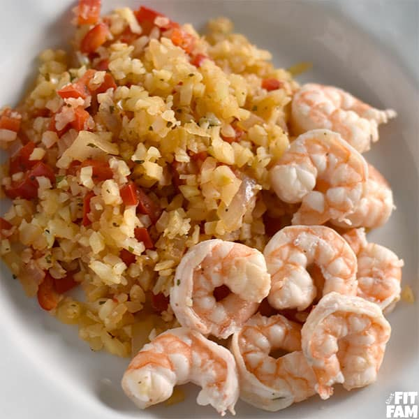 a plate of shrimp with some cauliflower rice on the side, seasoning is cajun