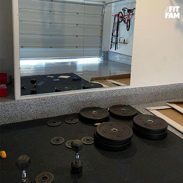 garage gym in progress. gym mirrors and floor mats